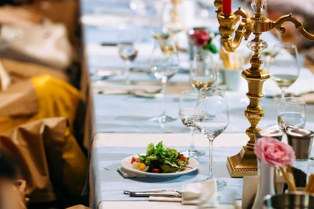 Сервированный банкетный столик с салатом