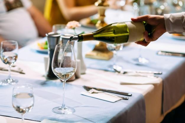 Рука официанта наливая вино в стеклянный накрытый стол
