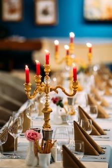 Сервированный банкетный стол с бокалами канделябра