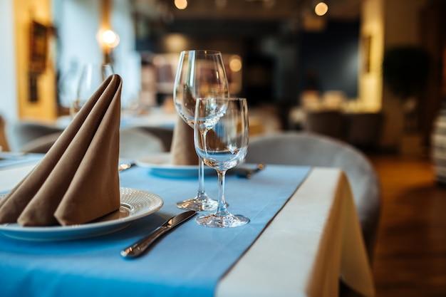 Сервированный банкетный столик в ресторане с бокалами