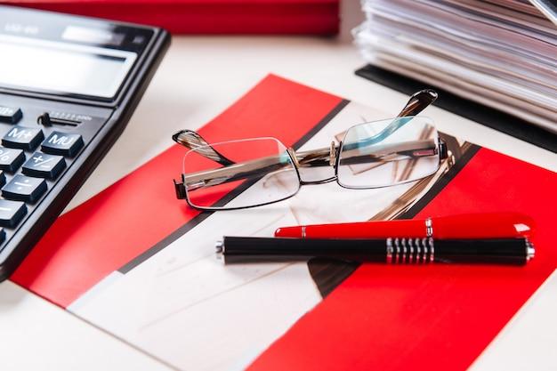 Очки, ручки калькулятор офисного рабочего стола стол