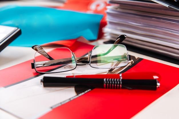 Офисное место папки стаканы красного цвета стол