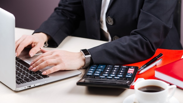 Офисные женские руки ноутбук калькулятор кофе