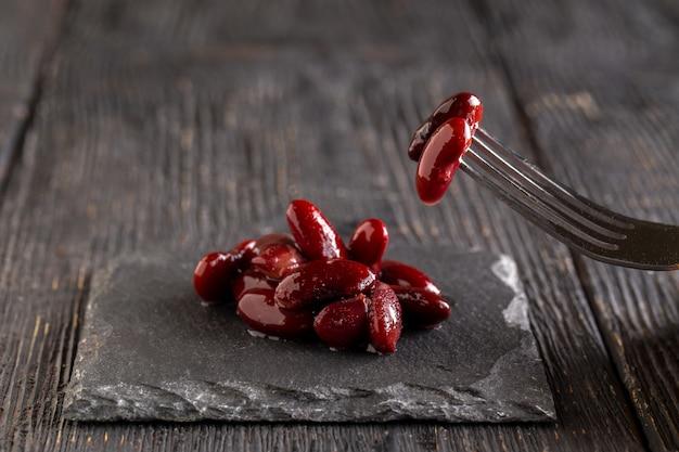 暗い木製のテーブルのブラックボードに自然調理された小豆を食べる