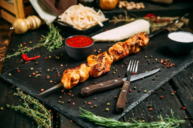 Аппетитный куриный шашлык на темной деревянной поверхности