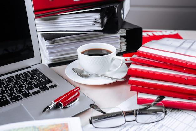 Офисное место для ноутбука сообщает о ручках, очках и кофе
