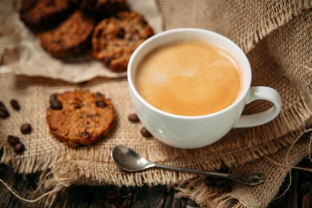 Вид сбоку кофе с печеньем на деревянный стол