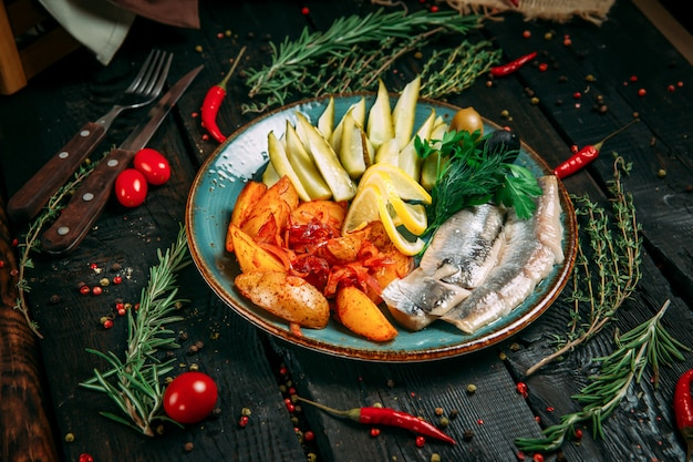 Русская закуска к алкоголю с картофелем, солеными огурцами и сельдью в синей тарелке на черном деревянном фоне