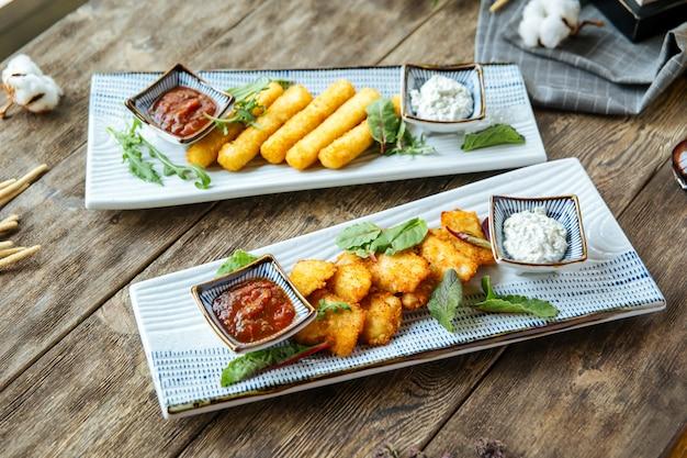 Жареные сырные палочки и куриные наггетсы с соусом