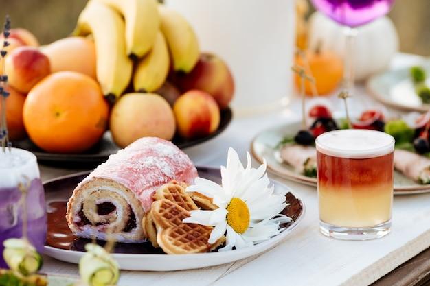 Десерт в тарелке. ролл и печенье. летний кейтеринг к празднику на белом деревянном столе.