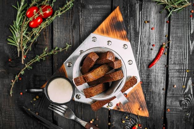トマトとハーブの木製の背景に三角形のボード上のソースの小さなバケツにシャキッとしたニンニクパン棒の平面図