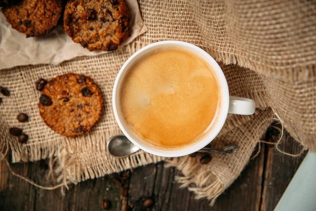 Вид сверху кофе с печеньем на деревянном столе