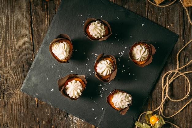 Вид сверху на сладкие десертные маффины со сливками