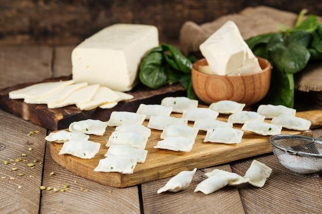 未調理のロシアの郷土料理ヴァレニキ餃子とチーズ、バター、ほうれん草。
