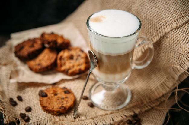 Латте маккиато с печеньем на деревянном столе