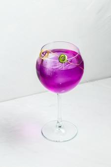 Необычный фиолетовый алкогольный коктейль в бокале