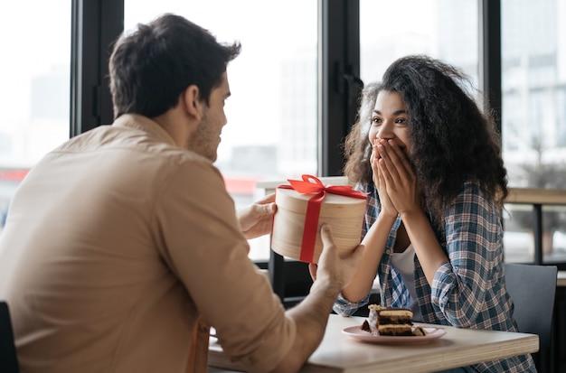 Азиатский мужчина дает подарок на день рождения красивой эмоциональной женщины