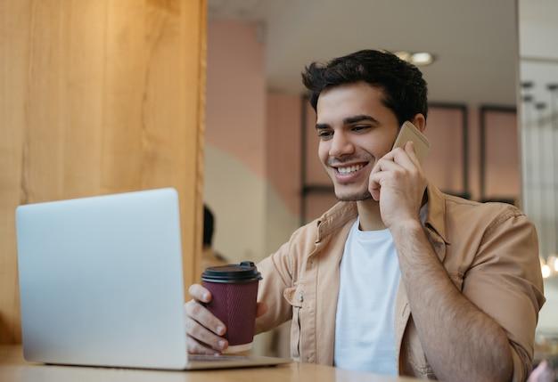 ハンサムなインドのビジネスマンが携帯電話で話している、一杯のコーヒーを保持している、自宅で仕事