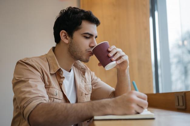 インドのビジネスマンがカフェでコーヒーを飲み、メモを取り、スタートアップを計画