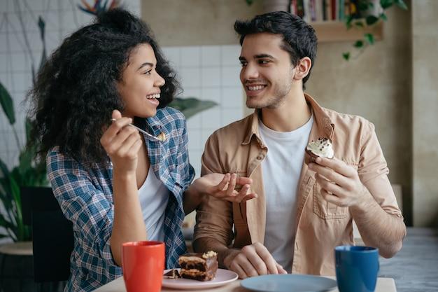 Счастливые многорасовые друзья общаются вместе, пьют кофе, едят торт, сидят в кафе