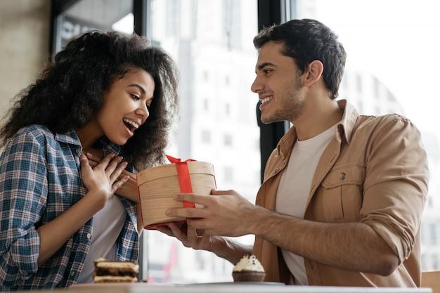 美しい女性に誕生日プレゼントを与える男。カフェで一緒に座って、デート多民族カップル