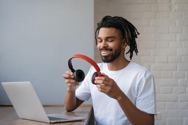 音楽を聴く、ワイヤレスヘッドフォンを保持している若いアフリカ系アメリカ人の男