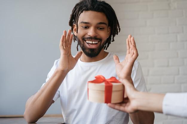 ギフト用の箱を探して幸せな感情的なアフリカ人