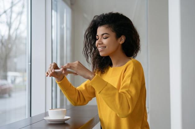 アフリカ系アメリカ人の食品ブロガーがカフェに座っている彼女のスマートフォンで写真を撮っています。