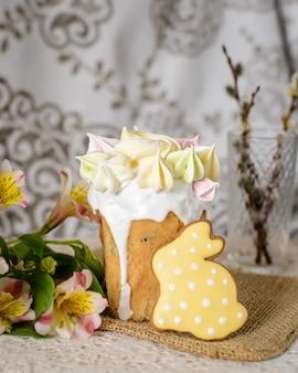 黄色のメレンゲとイースターのお祝いのためのウサギの形をした黄色のジンジャーブレッドで飾られたイースターケーキ