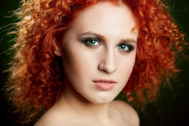 Девушка с длинными и блестящими волнистыми рыжими волосами. красивая модель с фигурной прической