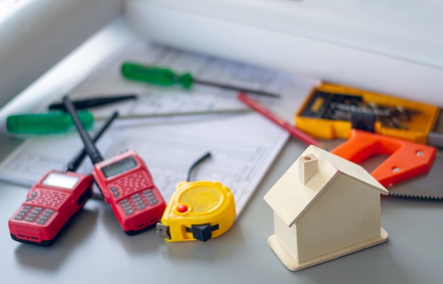 建設および家の改修のコンセプト、モデルハウス、作業ツール、家の鍵、デスクトップ上のドラフトプロジェクト