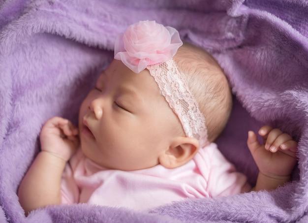 ピンクの花のヘッドバンドを身に着けている毛皮で覆われた布で寝ているかわいいアジアの新生児の女の子。