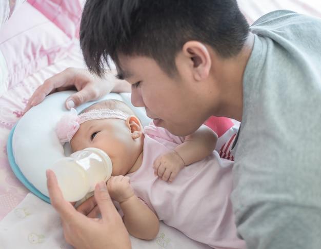 Отец кормит своего ребёнка бутылочкой дома в спальне