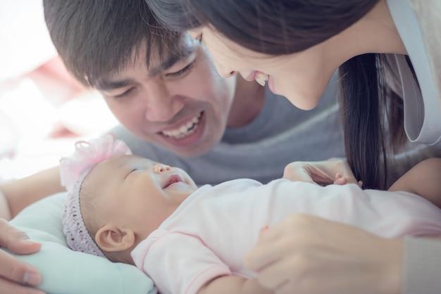 ママとパパと日当たりの良い部屋で遊ぶ赤ちゃん。親と子が家でのんびり。家族で一緒に楽しんで。