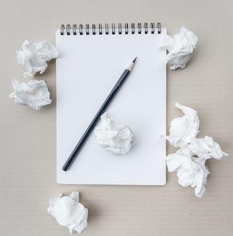 Написание концепции - мятые бумажные комки с листом белой бумаги и карандашом