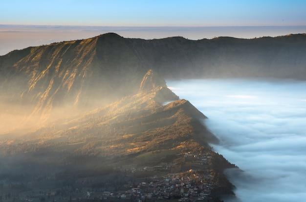 日の出時の背景にあるブロモ火山の隣の村、ブロモテンガーセメル国立公園のブロモ山にあるセモロラワン村、