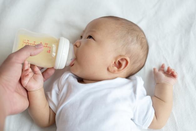 自宅の寝室でボトルを赤ちゃんに授乳する手。