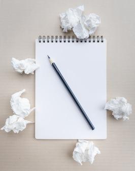 Написание концепции - мятые бумажные комки с листом белой бумаги и карандашом.