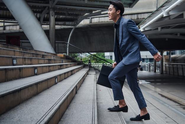 市、ビジネスコンセプトの成長の階段で歩くビジネスマン