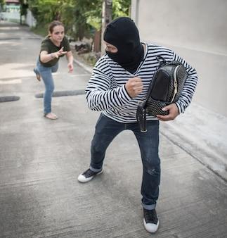 強盗が路上の女性からお金とバッグをひったくり。泥棒のお金の概念