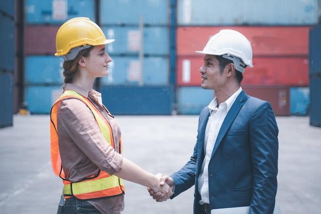 コンテナー貨物で成功するために握手するエンジニアスタッフ