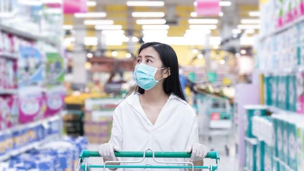 スーパーマーケットのデパートでショッピングマスクを身に着けている新しい通常の女性アジア