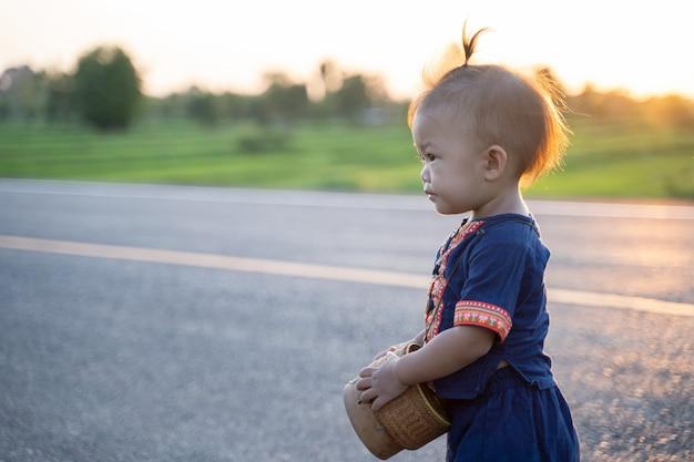 小さな子供女の子は、プエタイスタイルのタイの伝統的なドレスを着ています。彼女の肩にプラエワシルクと髪飾りを身に着けて、特別なイベントでユニークな地元の文化をドレスアップします