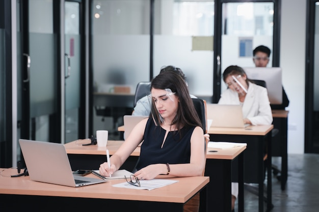 社会的距離と新しい通常のポリシーに従ってコワーキングスペースで働くコロナウイルスの時間ビジネス女性