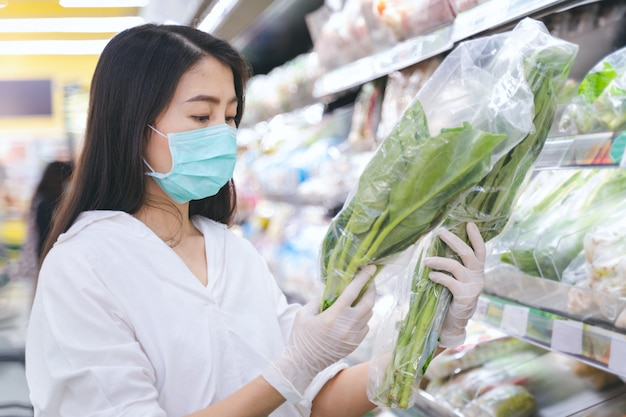 身に着けている女性は、食料品店で食料品、果物や野菜を買い物にフェイスマスクとゴム手袋を保護します。