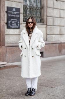 寒い冬の雪の日に通りを歩いて美しいスタイリッシュな女性。黒のブラウスとズボンと白い毛皮のコートを着ているファッショナブルな女の子。