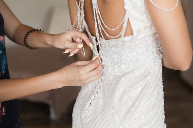 ガールフレンドのボタンを押すのを助ける白い花嫁介添人ドレス