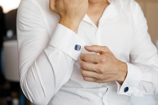 白いシャツとカフスボタンを身に着けている手の男のクローズアップ