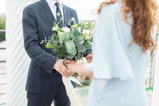 豪華な結婚式のアーチの通路で手を繋いでいる幸せなカップル