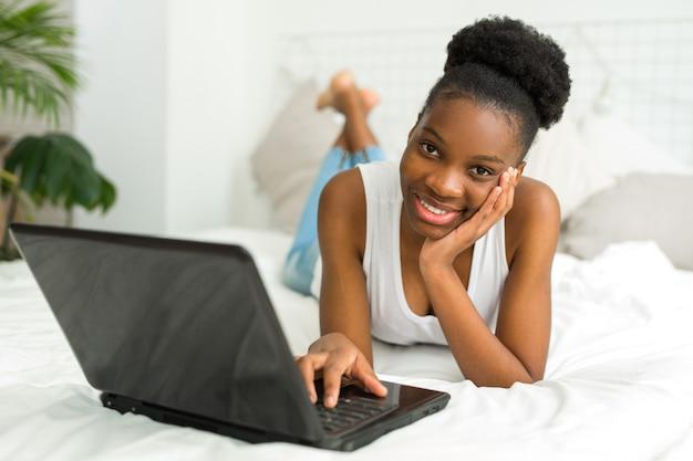 Красивая молодая африканская женщина лежит на кровати с ноутбуком